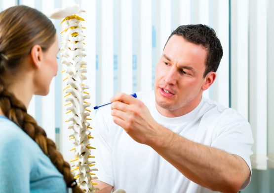 Physiotherapist in his practice, he explains a female patient the vertebral column and the emergence of back pain fizyoterapist, o bir kadınhastaya vertebral sütunu ve sırt ağrısının ortaya çıkışını açıklıyor